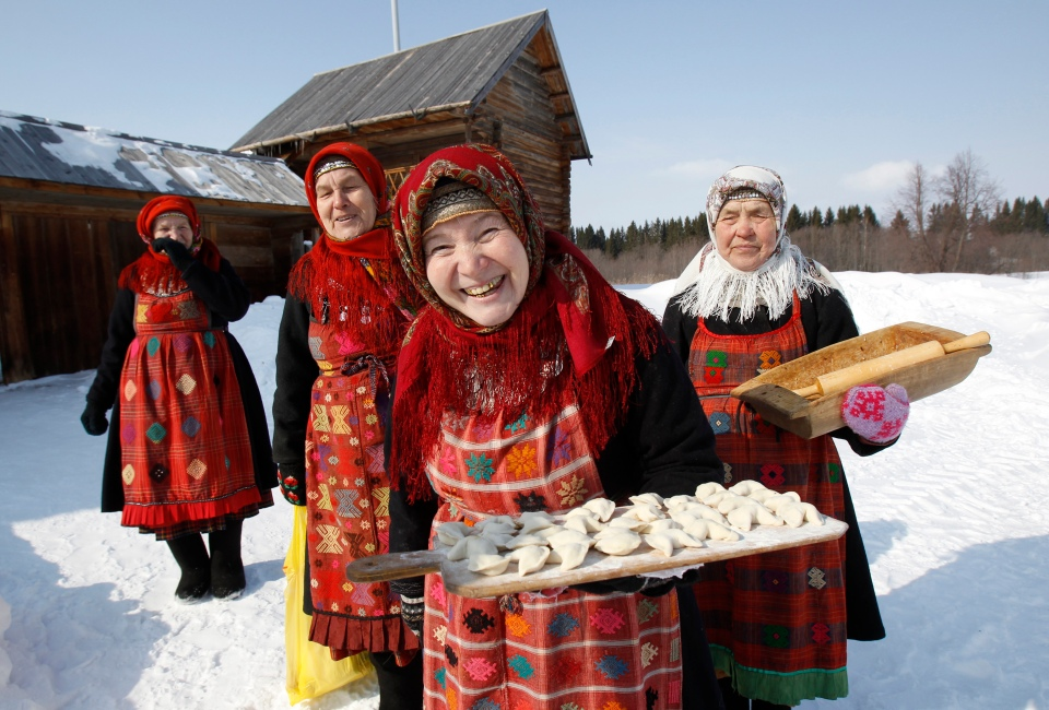 "Byagisheva, Shklayeva, Dorodova and Baisarova, members of the singing group ""Buranovskiye Babushki"", offer home made dumplings at a folk museum near the village of Ludorvai"
