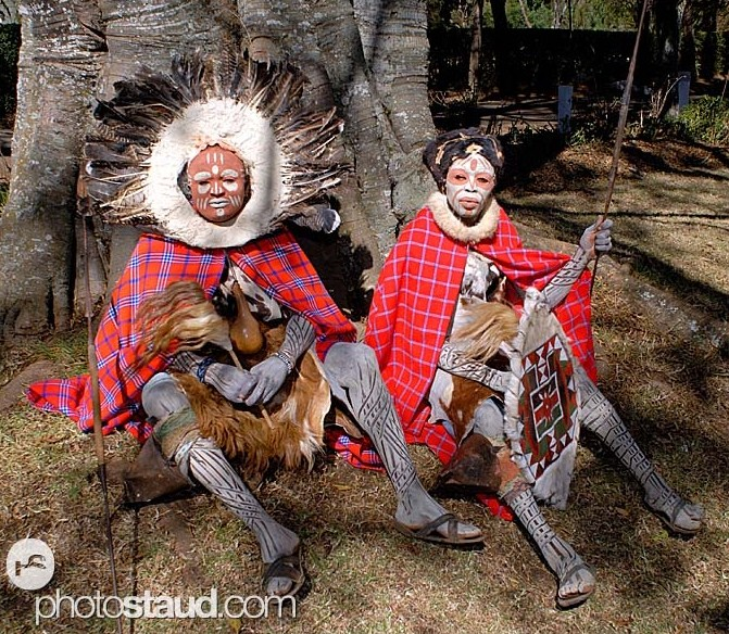 Kikuyu dancers wearing traditional costumes sitting under tree, Kenya
